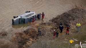 Rescue crews attempt to remove a van that was swept into the Grand River on Wednesday, Feb. 21, 2018.