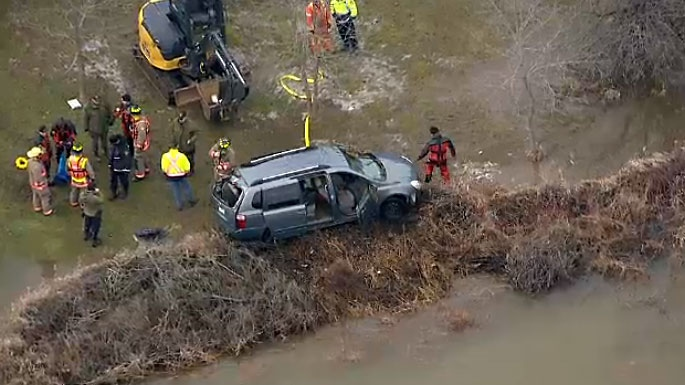 Crews pull a van from Grand River near Orangeville after it was swept into the water with a woman and child inside.