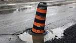 A pilon alerts motorists to a large pothole on Colonel By Drive in Ottawa on Wednesday, Feb. 21, 2018.