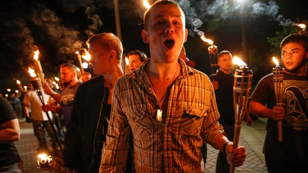 In this photo taken Friday, Aug. 11, 2017, multiple white nationalist groups march with torches through the UVA campus in Charlottesville, Va. (Mykal McEldowney / The Indianapolis Star via AP)