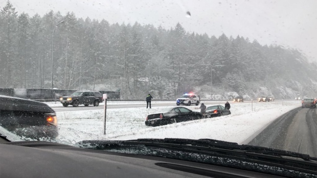 Two cars could be seen in a ditch between the north and south lanes of the Trans-Canada Highway near Thetis Lake Regional Park as heavy snow fell on the region. Feb. 21, 2018. (Twitter/@BrentDargis)