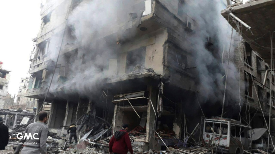 In this photo released on Wednesday Feb. 21, 2018, provided by the Syrian anti-government activist group Ghouta Media Center, which has been authenticated based on its contents and other AP reporting, shows Syrians gather next of a destroyed building that attacked by Syrian government forces airstrikes, in Ghouta, a suburb of Damascus, Syria. (Ghouta Media Center via AP)