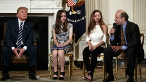From left, U.S. President Donald Trump, Marjory Stoneman Douglas High School student students Carson Abt, and Ariana Klein, listen as Carson's father Frederick Abt, speaks during a listening session with high school students, teachers, and others in the State Dining Room of the White House in Washington on Wednesday, Feb. 21, 2018. (AP Photo/Carolyn Kaster)