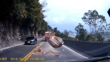 Boulder falls, almost hits vehicles