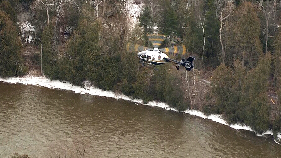 A helicopter is seen flying over the Grand River near Waldemar, Ont., Thursday, Feb. 22, 2018.