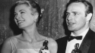 FILE - In this March 31, 1955 file photo, Grace Kelly, left, and Marlon Brando, hold their best actress and actor Oscars in Los Angeles. Kelly's icy green satin gown was designed by Edith Head. (AP Photo, File)