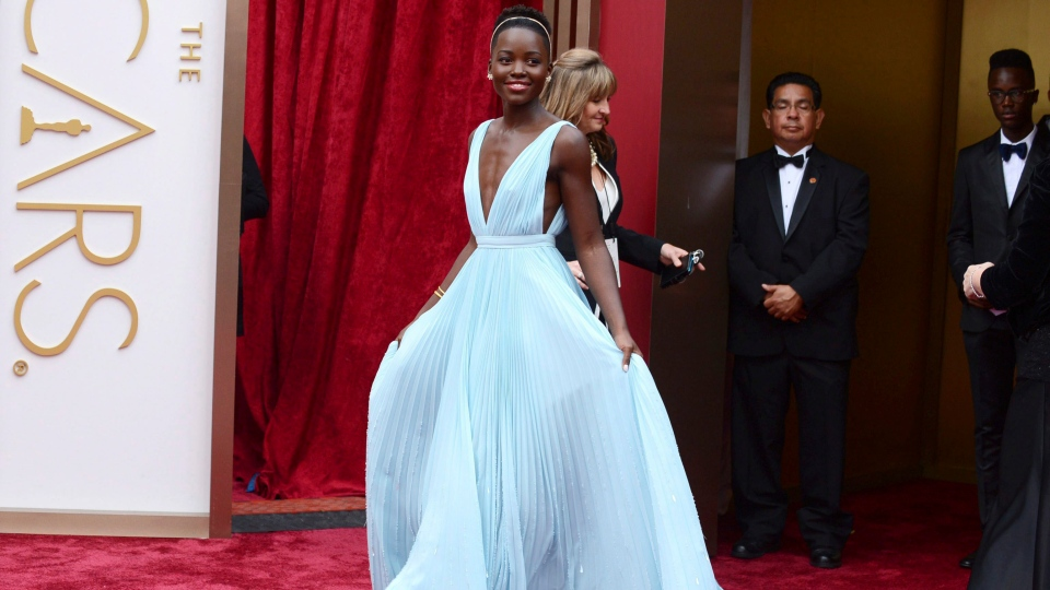"FILE - In this March 2, 2014 file photo, Lupita Nyong'o arrives at the Oscars in Los Angeles. Nyong'o, wearing a light blue Prada gown, won the Oscar for best supporting actress for her role in ""12 Years a Slave."" (Photo by Jordan Strauss/Invision/AP, File)"