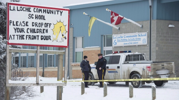 Members of the RCMP stand outside the La Loche Community School in La Loche, Sask. Monday, Jan. 25, 2016. THE CANADIAN PRESS/Jonathan Hayward