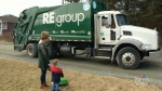 Hiro Getson, 3, and his mom check out a garbage truck at the end of their driveway.