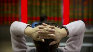A Chinese investor monitors stock prices at a brokerage house in Beijing, Friday, Feb. 23, 2018. (AP Photo/Mark Schiefelbein)