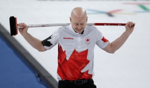 Canada's skip Kevin Koe holds his broom during the men's bronze medal curling match against Switzerland at the 2018 Winter Olympics in Gangneung, South Korea on Friday, Feb. 23, 2018. (AP Photo/Natacha Pisarenko)