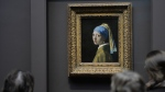 The luminescent tableau painted by Dutch master Johannes Vermeer around 1665 was last examined in 1994 .(© AFP PHOTO/Stan HONDA)