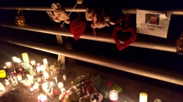 Candles and flowers sit on a bridge near the Grand River where three-year-old Kaden Young was swept into and has not yet been found.
