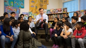 Federal Finance Minister Bill Morneau is joined by students from Toronto's Rose Avenue Junior Public School and his adopted daughter Grace as he tries on a pair of shoes during a pre-budget photo opportunity in Toronto on Friday February 23, 2018. THE CANADIAN PRESS/Chris Young