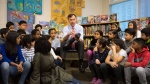 Federal Finance Minister Bill Morneau is joined by students from Toronto's Rose Avenue Junior Public School and his adopted daughter Grace as he tries on a pair of shoes during a pre-budget photo opportunity in Toronto on Friday, Feb. 23, 2018. THE CANADIAN PRESS/Chris Young