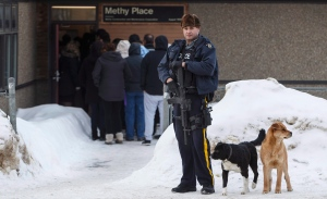 A police officer stands guard outside court in La Loche, Sask., before a judge delivers what's expected to be a decision on whether or not the La Loche shooter be sentenced as an adult Friday Feb. 23, 2018. THE CANADIAN PRESS/Jason Franson