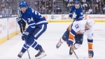 Toronto Maple Leafs' Auston Matthews (left) takes the puck away from New York Islanders' Casey Cizikas during second period NHL hockey action in Toronto, on February 22, 2018.THE CANADIAN PRESS/Chris Young