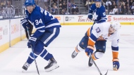 Toronto Maple Leafs' Auston Matthews (left) takes the puck away from New York Islanders' Casey Cizikas during second period NHL hockey action in Toronto, on Thursday, February 22, 2018.THE CANADIAN PRESS/Chris Young