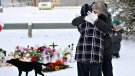 People embrace at a memorial in La Loche in this file photo.