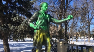 The statue of Sir John A. MacDonald is shown with green and silver paint on Feb. 23, 2018 (Creeson Agecoutay / CTV Regina)