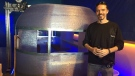 Randy Janes, owner of Wave of the Future 3D and co-owner of Create Cafe, poses in front of what's being dubbed the first 3D-printed camper in the world. It was printed in Saskatoon. (Ashley Field/CTV Saskatoon)