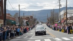 People line the street to pay respects as the hearse carrying the body of Rev. Billy Graham travels through Black Mountain, N.C., Saturday, Feb. 24, 2018. The procession is part of more than a week of mourning that culminates with his burial next week at his library in Charlotte. (AP Photo/Kathy Kmonicek, Pool)