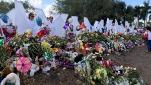 Seventeen people dressed as angels stand Sunday, Feb. 25, 2018, at the memorial outside Marjory Stoneman Douglas High School in Parkland, Fla., for those killed in a shooting on Feb. 14. (AP Photo/Terry Spencer)