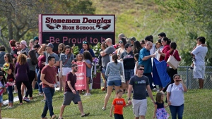 Parents and students arrive at Marjory Stoneman Douglas High School for an open house on Sunday, Feb. 25, 2018, in Parkland, Fla., as parents and students returned to the school for the first time since over a dozen were killed on Feb. 14. (David Santiago / Miami Herald via AP)