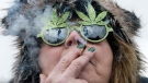 The Peace Tower is reflected in the sunglasses of a woman smoking a joint during a marijuana rally on Parliament HIll in Ottawa on April 20, 2013. (Justin Tang / THE CANADIAN PRESS)