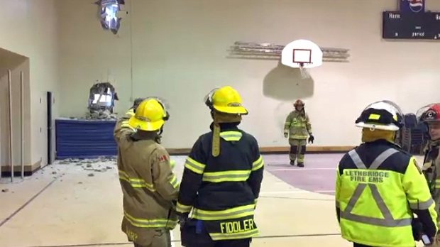 Emergency crews inspect the two holes in the wall of the Sik-Ooh-Kotoki Frienship Centre gymnasium following Monday's derailment