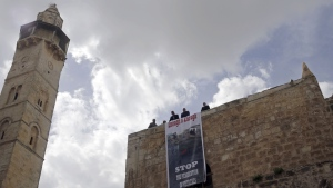 A protest sign hangs outside of the Church of the Holy Sepulchre, traditionally believed by many Christians to be the site of the crucifixion and burial of Jesus Christ, in Jerusalem, Sunday, Feb. 25, 2018. (AP Photo/Mahmoud Illean)