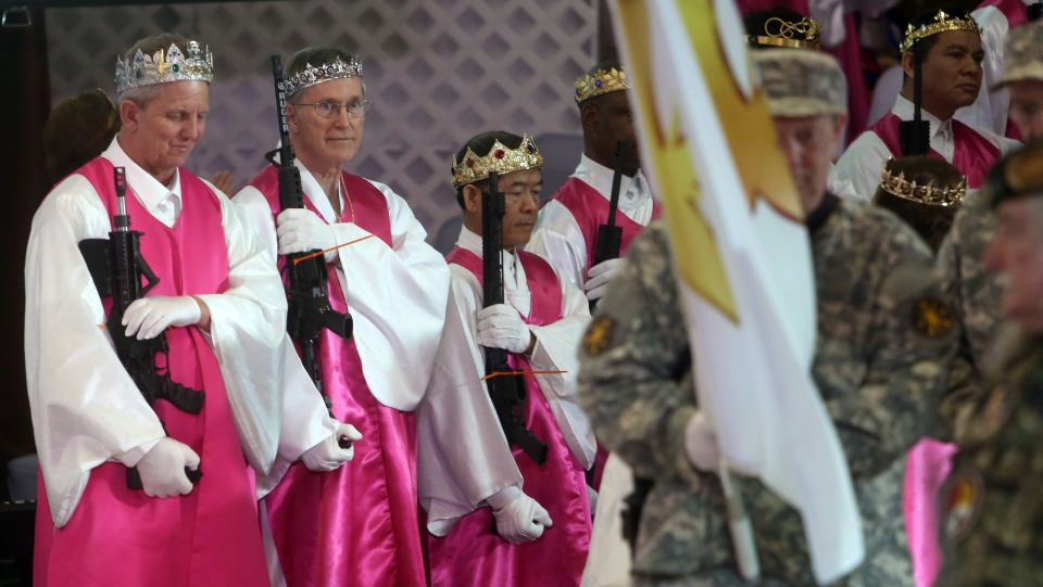 Men wear crowns and hold unloaded weapons at the World Peace and Unification Sanctuary, Wednesday Feb. 28, 2018 in Newfoundland, Pa. Worshippers clutching AR-15 rifles participated in a commitment ceremony at the Pennsylvania-based church. (AP Photo/Jacqueline Larma)