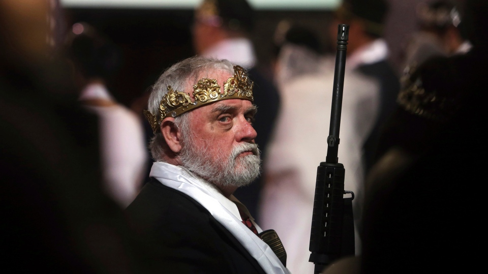 A man wears a crown and holds an unloaded weapon at the World Peace and Unification Sanctuary, Wednesday, Feb. 28, 2018, in Newfoundland, Pa. (AP Photo/Jacqueline Larma)