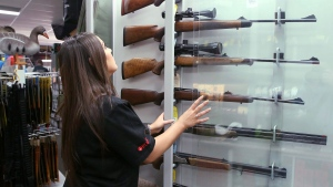 Salesperson Lauren Ungari checks rifles in a display in a gun shop in Sydney, Australia, Wednesday, Oct. 4, 2017. (AP Photo/Rick Rycroft)