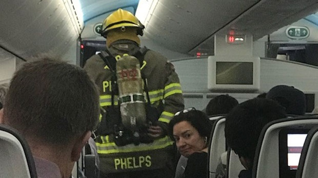 A firefighter is seen on board an Air Canada plane after a passenger's cellphone caught fire.