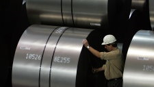 A steel worker measures steel coils of ThyssenKrupp steel company in Duisburg, western Germany on Sept. 22, 2005. (AP Photo/Frank Augstein, File)