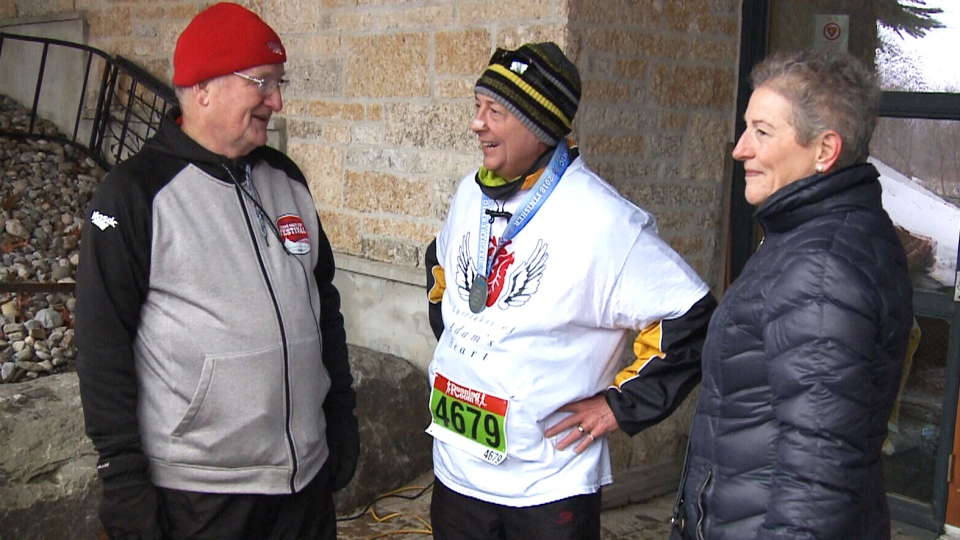 John Dickhout (centre) stands with Adam's father, Rick Prashaw (left), after completing the 10-kilometre race.