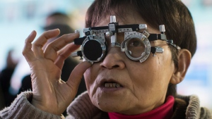 Bao Qin Song reads the letters on an eye chart while being examined at a makeshift eye clinic in the Downtown Eastside of Vancouver, B.C., on Sunday March 4, 2018.  THE CANADIAN PRESS/Darryl Dyck