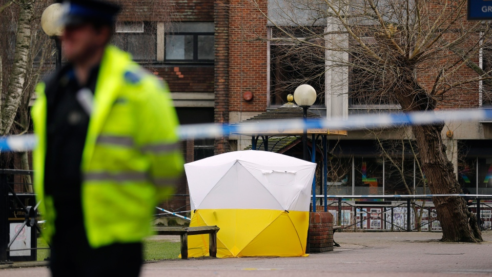"Police officer secures the area as a police tent covers the the spot in Salisbury, England, Tuesday, March 6, 2018, where former Russian spy double agent Sergei Skripal and his companion were found critically ill Sunday following exposure to an ""unknown substance"". (AP Photo/Frank Augstein)"
