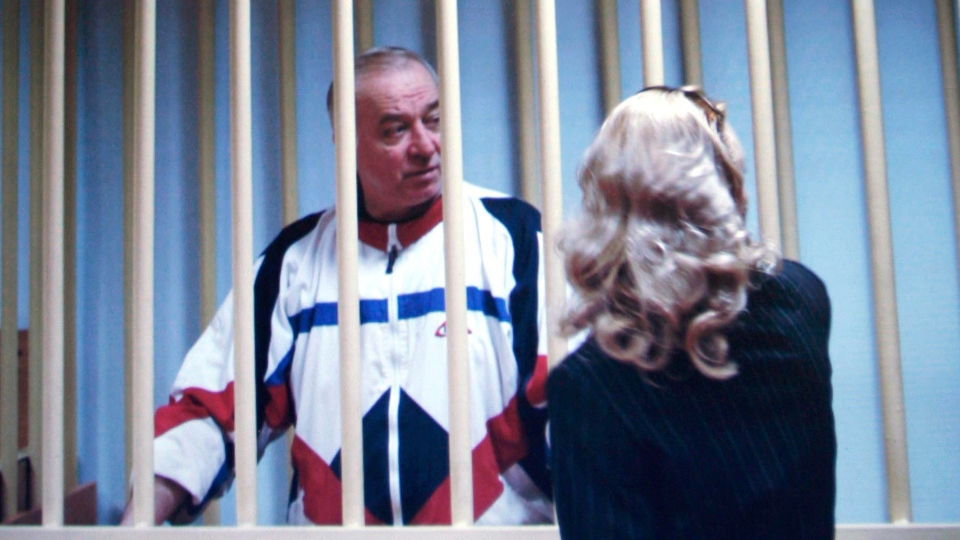 Sergei Skripal speaks to his lawyer from behind bars seen on a screen of a monitor outside a courtroom in Moscow, Wednesday, Aug. 9, 2006. (AP / Misha Japaridze)