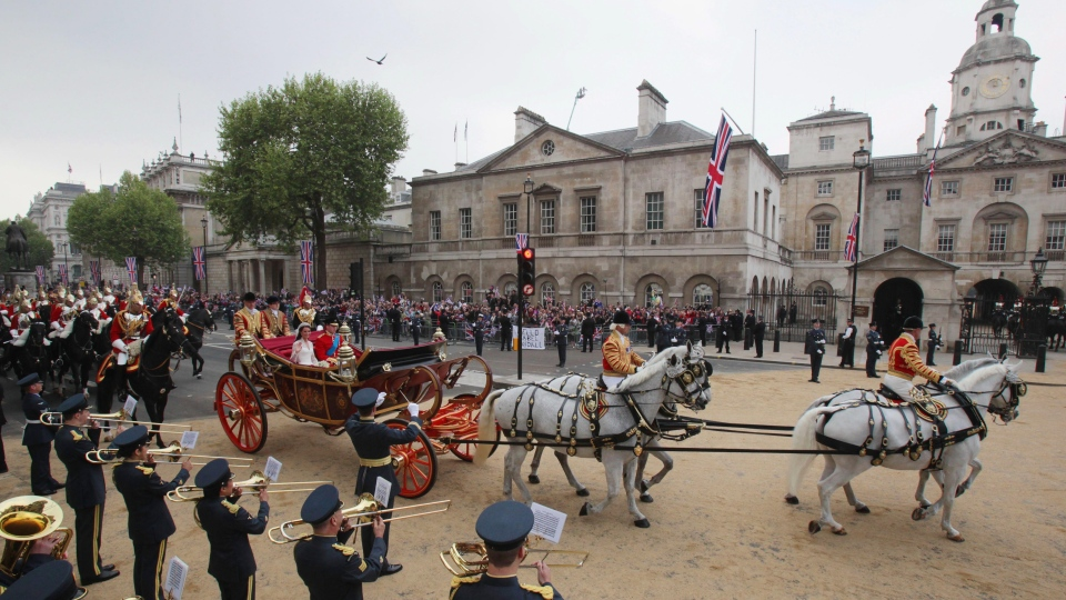 In this file photo, Prince William and Kate, the Duchess of Cambridge, wave as they travel in the 1902 State Landau carriage along the processional route to Buckingham Palace, London, Friday April 29, 2011. (AP Photo/Matt Cardy)