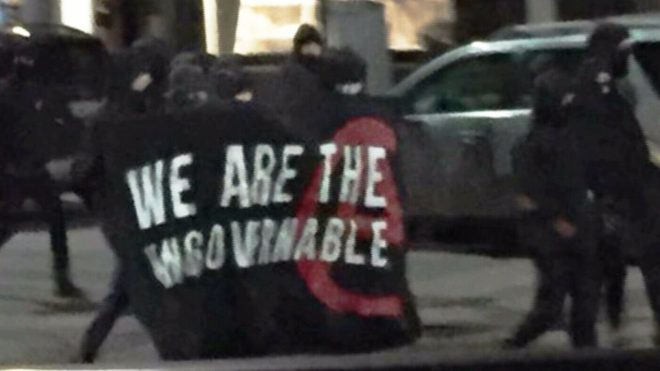 """Masked individuals carrying a banner that says """"We Are the Ungovernables"""" are seen on Locke Street in Hamilton on Mar. 3, 2018. (CTV News Toronto)"""