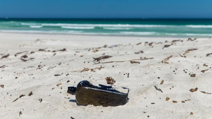 A bottle tossed overboard by a German sailor in 1886 is shown on a beach in Australia where it was found. (Kym Illman)