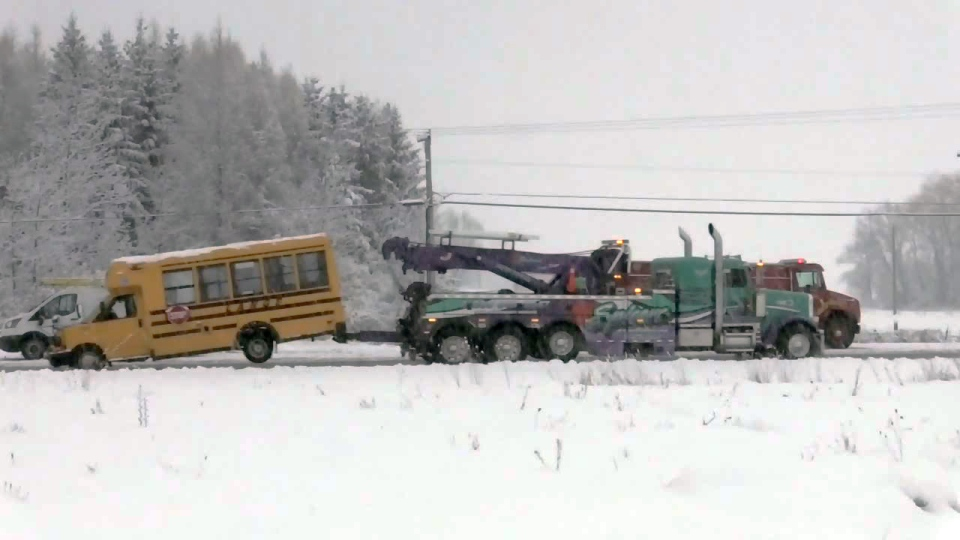 A school bus is towed away from the scene of a collision on Oxford Road 29, west of Drumbo, on Wednesday, March 7, 2018.
