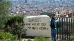 A tourist takes a picture of the city's panorama as he stands next to a wall with graffiti reading 'Tourist: your luxury trip - my daily misery' at Park Guell in Barcelona. (Josep LAGO / AFP)