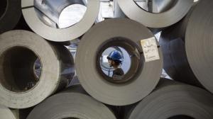 In this Feb. 20, 2018, photo, crane operator Benjamin Ruiz, 25, of Camden, works to move 40,000 pound slit coils inside Camden Yards Steel in Camden, N.J.  (Joe Lamberti/Camden Courier-Post via AP)