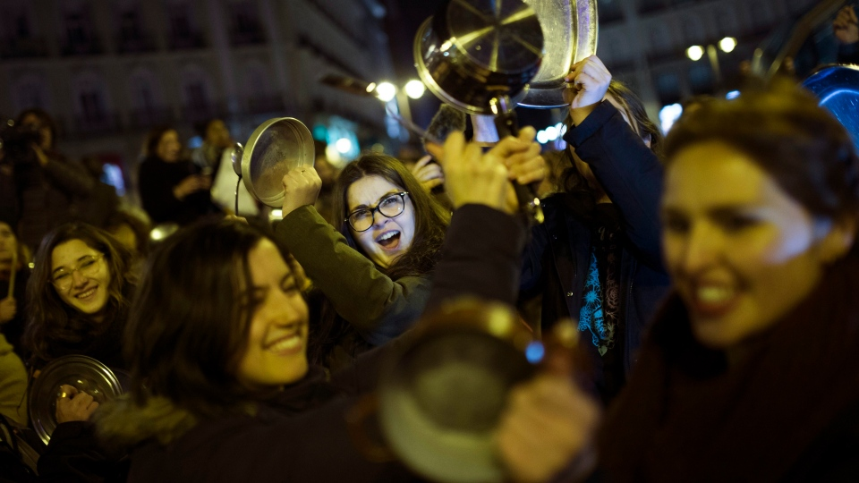 Women bang pots and pans as shooting slogans during a protest marking the beginning of a 24-hour women strike at the Sol square in Madrid, early Thursday, March 8, 2018. (AP Photo/Francisco Seco)