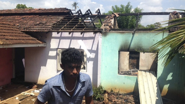 A Sri Lankan walks past a burnt house in Pallekele, Sri Lanka, Thursday, March 8, 2018. (Bharatha Mallawarachchi / AP)
