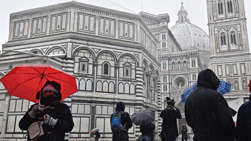 Tourists in Piazza del Duomo square with Santa Maria del Fiore Basilica and the Battistero, left, during a snowfall in Florence, Italy, on March 1, 2018. (Maurizio degl'Innocenti/ANSA via AP)