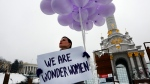 A woman holds balloons and a poster to mark International Women's Day in central Kiev, Ukraine, Thursday, March 8, 2018. (AP Photo/Efrem Lukatsky)